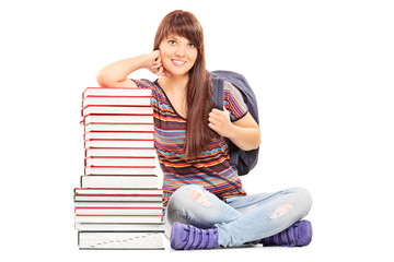 Female student leaning on a pile of books