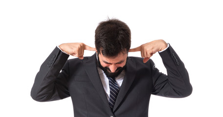 Businessman covering his ears over white background