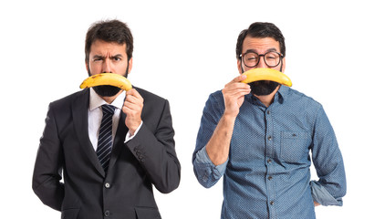 Sad brothers with bananas over white background