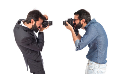 Man photographing at his brother over white background
