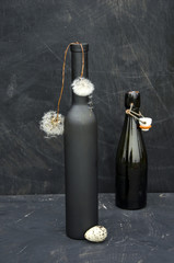 still-life with black bottles and dandelion seeds