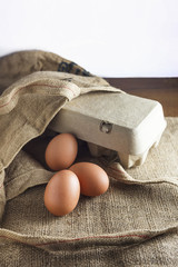 Eggs with paper pack in sack bag on wooden table