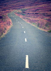 A curly long deserted road in the middle of nowhere with a nice
