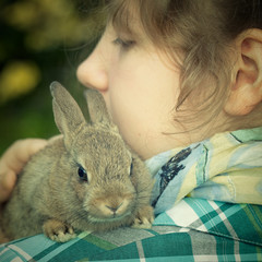 A teenage girl holding a bunny rabbit on her shoulder