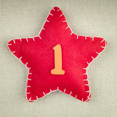 Red star with wooden number 1 on vintage fabric background