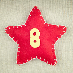 Red star with wooden number 8 on vintage fabric background