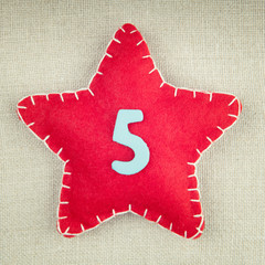 Red star with wooden number 5 on vintage fabric background
