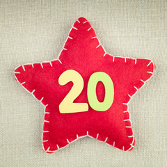 Red star with wooden number 20 on vintage fabric background