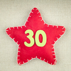 Red star with wooden number 30 on vintage fabric background