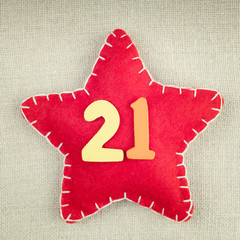 Red star with wooden number 21 on vintage fabric background