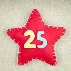 Concept for christmas, red star with wooden numbers 25 on vintag