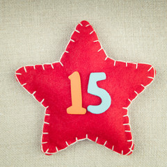 Red star with wooden number 15 on vintage fabric background