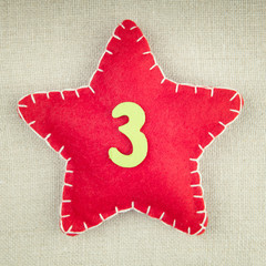 Red star with wooden number 3 on vintage fabric background