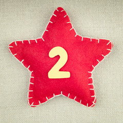 Red star with wooden number 2 on vintage fabric background