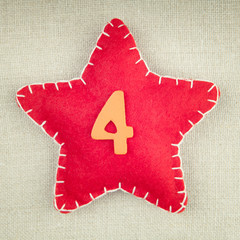 Red star with wooden number 4 on vintage fabric background