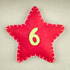 Red star with wooden number 6 on vintage fabric background