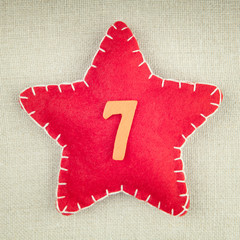 Red star with wooden number 7 on vintage fabric background