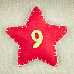Red star with wooden number 9 on vintage fabric background