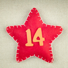 Red star with wooden number 14 on vintage fabric background