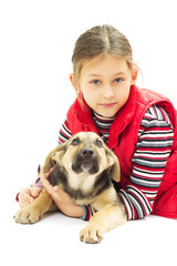 little girl in a red vest hugs his dog on a white background iso