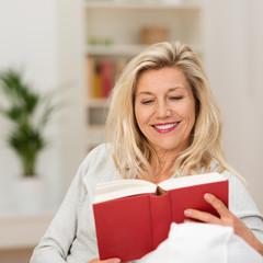 best-ager frau liest ein buch zu hause auf dem sofa