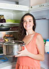 woman with saucepan  near refrigerator