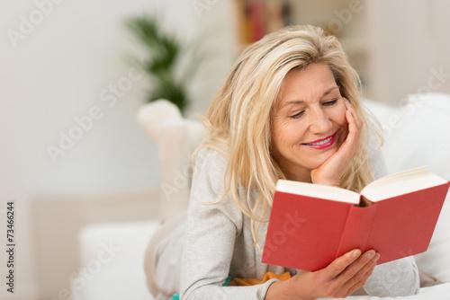 frau liegt auf dem sofa und liest ein buch - 73466244