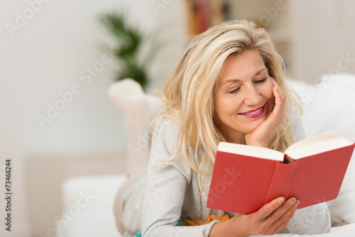 Leinwandbild Motiv frau liegt auf dem sofa und liest ein buch