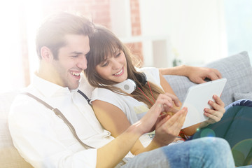 Young trendy couple having fun websurfing with tablet