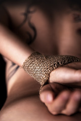 Rückenansicht einer nackten Frau mit gefesselten Händen