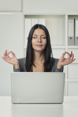 Junge Büroangestellte macht Yoga im Büro