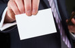 A businessman holding a blank business card.