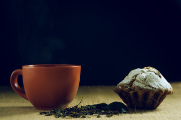 cup of green tea with cake on burlap background