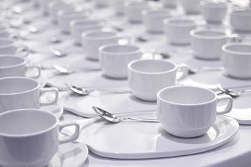 Stacks of coffee cups  with silver teaspoons  prepare for meetin