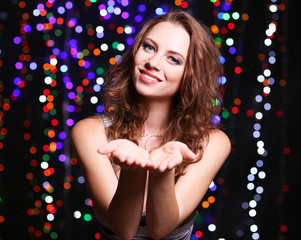 Portrait of beautiful young female on bright lights background