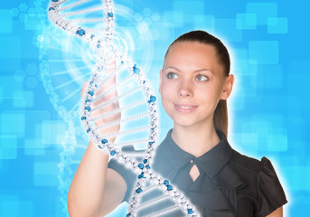 Girl looks at model of DNA and presses her finger