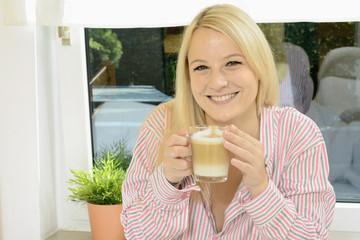 Frau im Pyjama trinkt Latte Macchiato