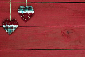 Red and green holiday hearts hanging on antique wood background