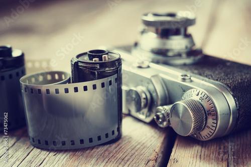 Leinwanddruck Bild Old photo film rolls, cassette and retro camera, selective focus