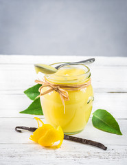 Jar of lemon curd with a spoon on rustic white wood background.