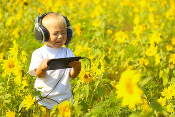 funny baby in headphones with a tablet