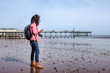 Woman using her mobile phone on the beach