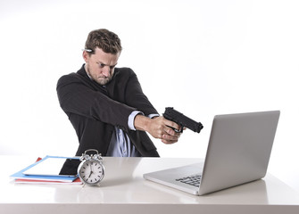 businessman pointing gun to computer in overwork overtime work