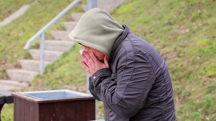 Cold man with napkin near nose at outdoors on the bench