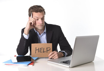 businessman working in stress at computer holding help sign