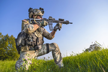 American Soldier aiming his rifle on blue sky background
