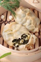 Two dumplings with greens and and cheese