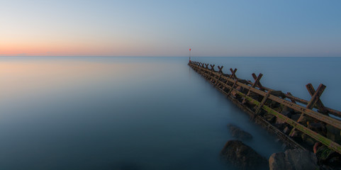 Breakwater, in a very calm sea, at sunrise