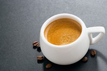 espresso on a dark background and coffee beans, top view