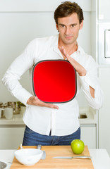 Man in the kitchen with red sign
